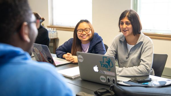 Three smiling students working together on computers